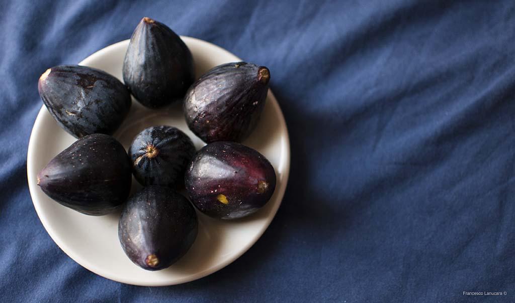 Un piatto di fichi neri su fondo blu